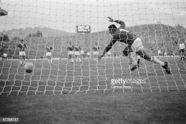 Swiss goalkeeper Charles Elsener fails to save Helmut Haller's penalty which is West Germany's fifth goal in their group B game against Switzerland...