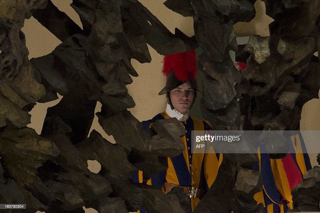 A Swiss guard is pictured through a sculpture during a private audience of the pope to members of the media on March 16, 2013 at the Paul VI hall at the Vatican. Pope Francis on Saturday called for 'a poor Church for the poor', saying he chose his papal name because St Francis of Assisi was 'a man of poverty and a man of peace'.