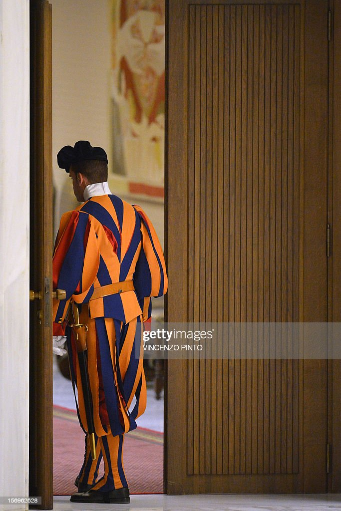 A Swiss guard stands at the entrance of the hall prior an audience with the pontif on November 26, 2012 at Paul VI hall at the Vatican. Pope Benedict XVI led an audience to the six non-European prelates appointed two-days ago as new members of the College of Cardinals.