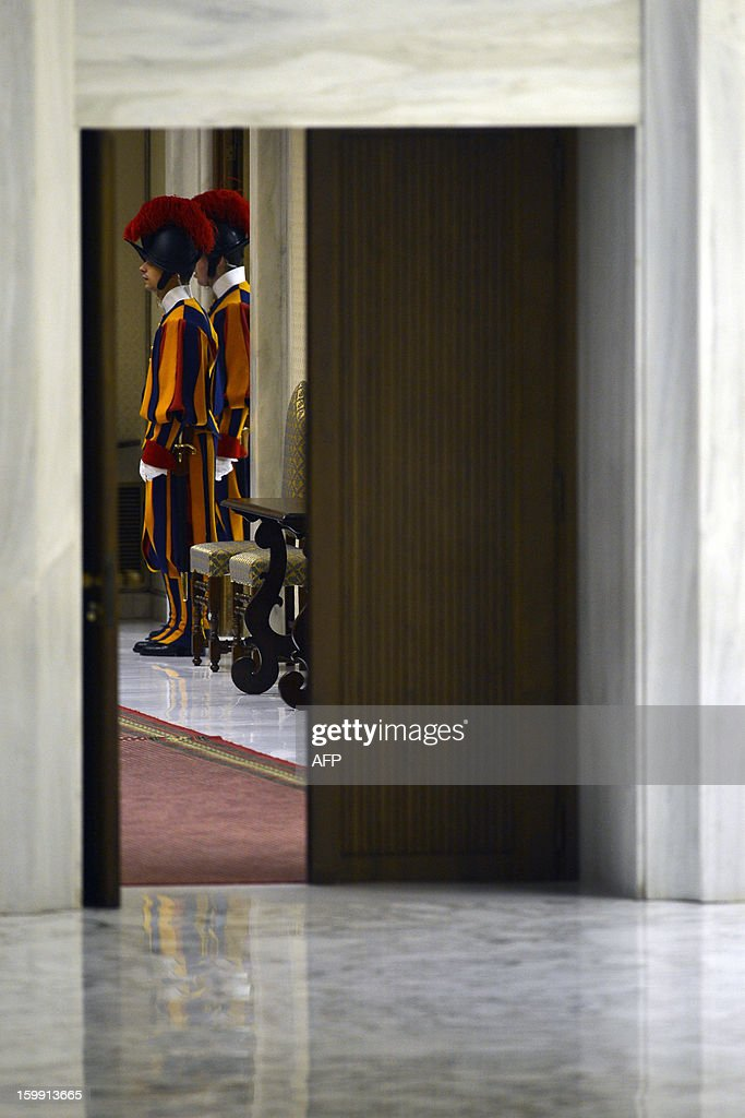 Swiss guards stand in a corridor during the pontif's weekly general audience on January 23, 2013 at the Paul VI hall at the Vatican.