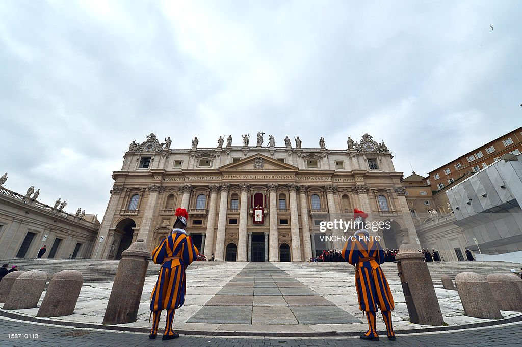 Swiss guards stand still as Pope Benedict XVI delivers his traditional Christmas 'Urbi et Orbi' blessing from the balcony of St. Peter's Basilica at the Vatican on December 25, 2012.