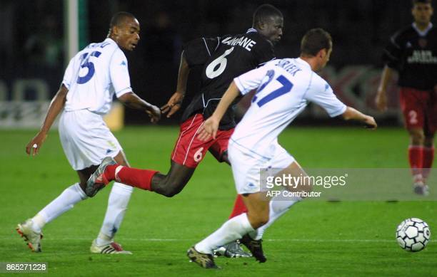 Swiss Kader Mangane fights for the ball with Auxerre midfielders Bonaventure Kalou and Pantxi Gilles Sirieix during their UEFA match AuxerreNeuchatel...