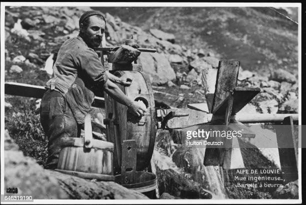 A Swiss man churns butter on the mountainside with an ingenious machine powered by a water wheel set in a mountain stream