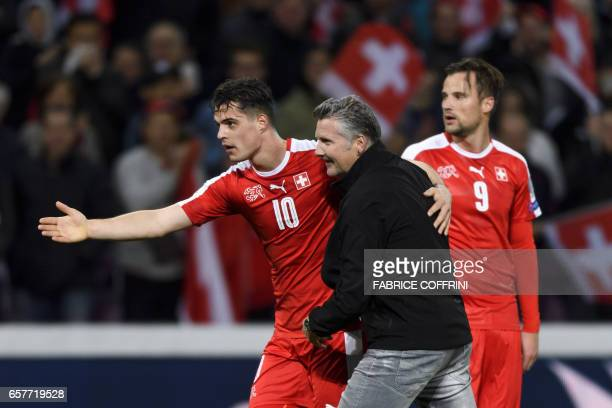 Swiss midfielder Granit Xhaka escorts a supporter who enters the pitch next to teammate forward Haris Seferovic during the FIFA World Cup 2018...