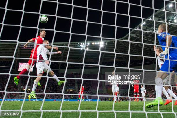 Swiss midfielder Josip Drmic heads the ball over Latvia's defender Aleksandrs Solovjovs to score the match's only goal during the WC 2018 qualifying...