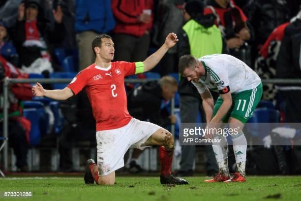 Swiss midfielder Stephan Lichtsteiner celebrates his team's qualification next to Northern Ireland's midfielder Chris Brunt at the end of the FIFA...