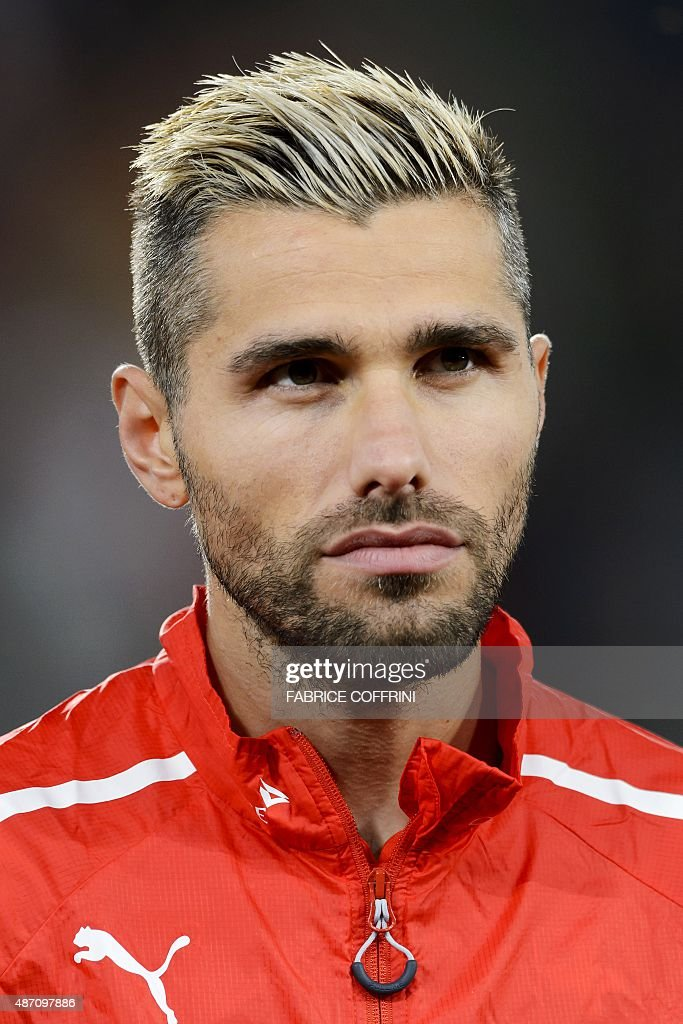 Swiss midfielder Valon Behrami stands during the national anthem prior to the Euro 2016 qualifying football match between Switzerland and Slovenia at the St. Jakob Park Stadium in Basel on September 5, 2015. Switzerland defeated Slovenia 3-2.