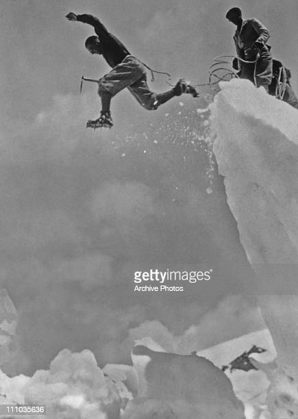 A Swiss mountaineer leaps over a crevasse in the Swiss Alps 5th December 1930