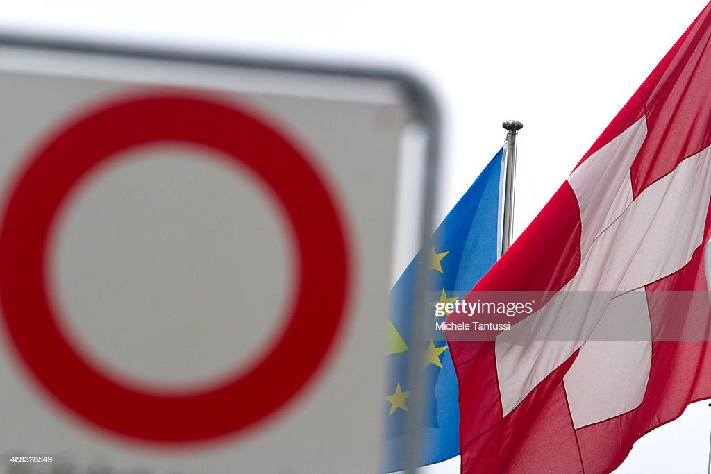 A swiss National Flag and an european Flag wave beside a road sign at the tree nations frontier on February 10, 2014 at Basel,Switzerland. Swiss citizens voted with a narrow majority in favour of measures to curb immigration from European Union countries in a move that will require Swiss officials to renegotiate several treaties with the EU. The referendum was launched by the right-wing Swiss People's Party (SVP). Approximately one quarter of people living in Switzerland are foreigners.