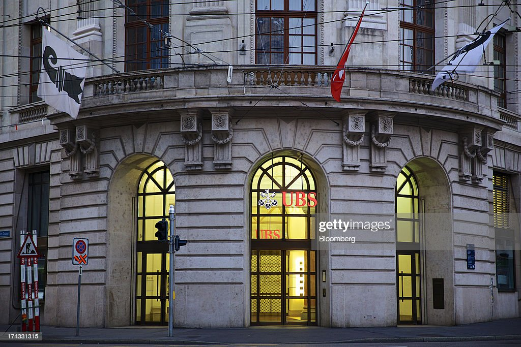 A Swiss national flag, center, flies over a branch of UBS AG in Basel, Switzerland, on Tuesday, July 23, 2013. Europe's biggest banks, which more than doubled their highest-quality capital to $1 trillion since 2007 to meet tougher rules, may have further to go as regulators scrutinize how lenders judge the riskiness of their assets. Photographer: Gianluca Colla/Bloomberg via Getty Images