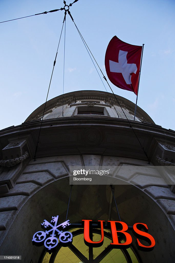 A Swiss national flag flies above the logo of UBS AG on display outside a branch of the bank in Basel, Switzerland, on Tuesday, July 23, 2013. Europe's biggest banks, which more than doubled their highest-quality capital to $1 trillion since 2007 to meet tougher rules, may have further to go as regulators scrutinize how lenders judge the riskiness of their assets. Photographer: Gianluca Colla/Bloomberg via Getty Images