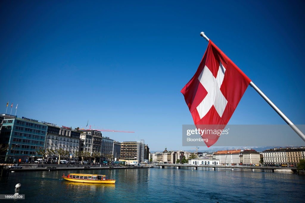 A Swiss national flag flies from a flagpole above Lake Geneva in Geneva, Switzerland, on Wednesday, June 5, 2013. Members of the Swiss parliament's upper house's economic committee have been debating a law which, if passed, could authorize Swiss banks to cooperate with U.S. authorities. Photographer: Valentin Flauraud/Bloomberg via Getty Images