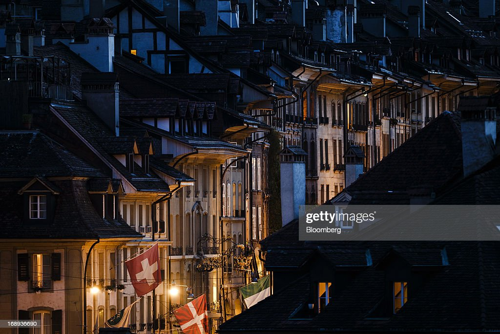 A Swiss national flag flies from a flagpole outside a house at night in the old town of Bern, Switzerland, on Monday, May 13, 2013. Risks to Switzerland's housing market increased further in the first three months of the year, raising the question as to whether authorities have taken sufficient steps to prevent the bursting of a bubble. Photographer: Valentin Flauraud/Bloomberg via Getty Images