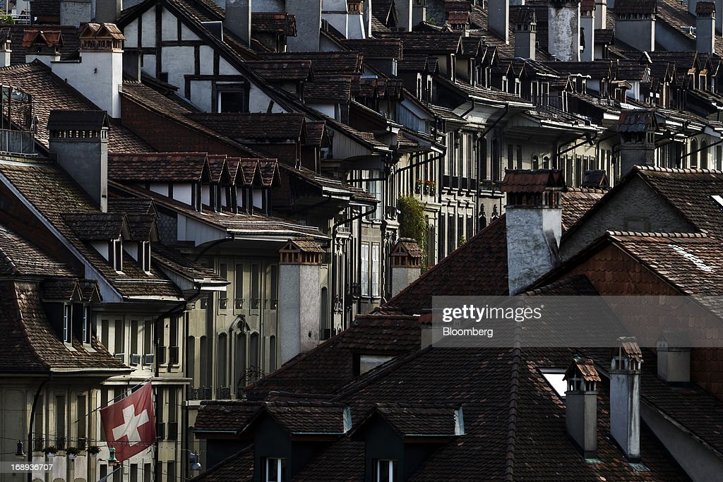 A Swiss national flag flies from a flagpole outside a house in the old town of Bern, Switzerland, on Monday, May 13, 2013. Risks to Switzerland's housing market increased further in the first three months of the year, raising the question as to whether authorities have taken sufficient steps to prevent the bursting of a bubble. Photographer: Valentin Flauraud/Bloomberg via Getty Images
