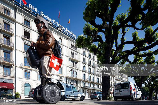 A Swiss national flag flies from a Segway as it passes the Bank Hapoalim Ltd private banking offices in Geneva Switzerland on Wednesday June 5 2013...