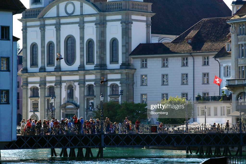 A Swiss national flag flies from the corner of a building as tourists stand on a bridge spanning the River Reuss in Lucerne, Switzerland, on Saturday, Aug. 10, 2013. The Swiss National Bank will abolish its franc ceiling once it starts raising interest rates, Vice President Jean-Pierre Danthine said. Photographer: Gianluca Colla/Bloomberg via Getty Images