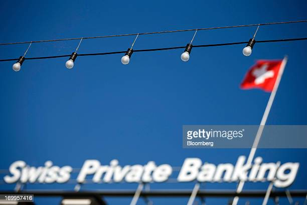 A Swiss national flag flies from the roof of the Bank Hapoalim Ltd private banking offices in Geneva Switzerland on Wednesday June 5 2013 Members of...