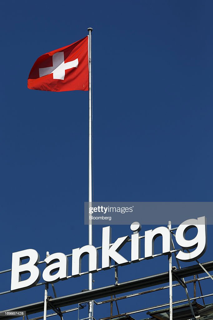 A Swiss national flag flies from the roof of the Bank Hapoalim (Switzerland) Ltd. (BHI) private banking offices in Geneva, Switzerland, on Wednesday, June 5, 2013. Members of the Swiss parliament's upper house's economic committee have been debating a law which, if passed, could authorize Swiss banks to cooperate with U.S. authorities. Photographer: Valentin Flauraud/Bloomberg via Getty Images