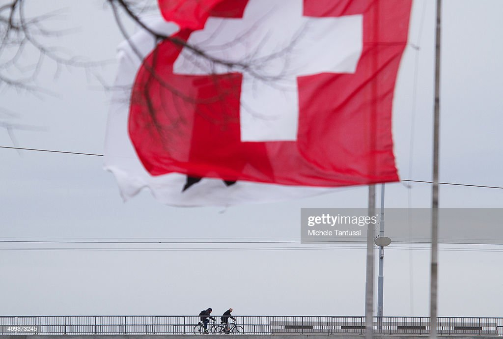 A Swiss National Flag waves as a Bikers cross the dreirosenbruecke or three roses Bridge between the tree nations frontier on February 14, 2014 at Basel,Switzerland. Swiss citizens voted with a narrow majority in favour of measures to curb immigration from European Union countries in a move that will require Swiss officials to renegotiate several treaties with the EU. The referendum was launched by the right-wing Swiss People's Party (SVP). Approximately one quarter of people living in Switzerland are foreigners.