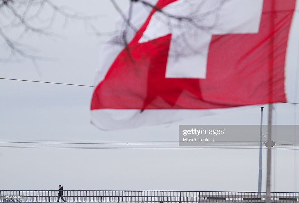 A Swiss National Flag waves as a pedestrian crosses the dreirosenbruecke or three roses Bridge between the tree nations frontier on February 14, 2014 at Basel,Switzerland. Swiss citizens voted with a narrow majority in favour of measures to curb immigration from European Union countries in a move that will require Swiss officials to renegotiate several treaties with the EU. The referendum was launched by the right-wing Swiss People's Party (SVP). Approximately one quarter of people living in Switzerland are foreigners.