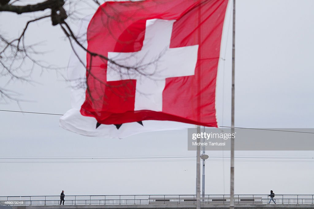 A Swiss National Flag waves as pedestrians cross the dreirosenbruecke or three roses Bridge between the tree nations frontier on February 14, 2014 at Basel,Switzerland. Swiss citizens voted with a narrow majority in favour of measures to curb immigration from European Union countries in a move that will require Swiss officials to renegotiate several treaties with the EU. The referendum was launched by the right-wing Swiss People's Party (SVP). Approximately one quarter of people living in Switzerland are foreigners.