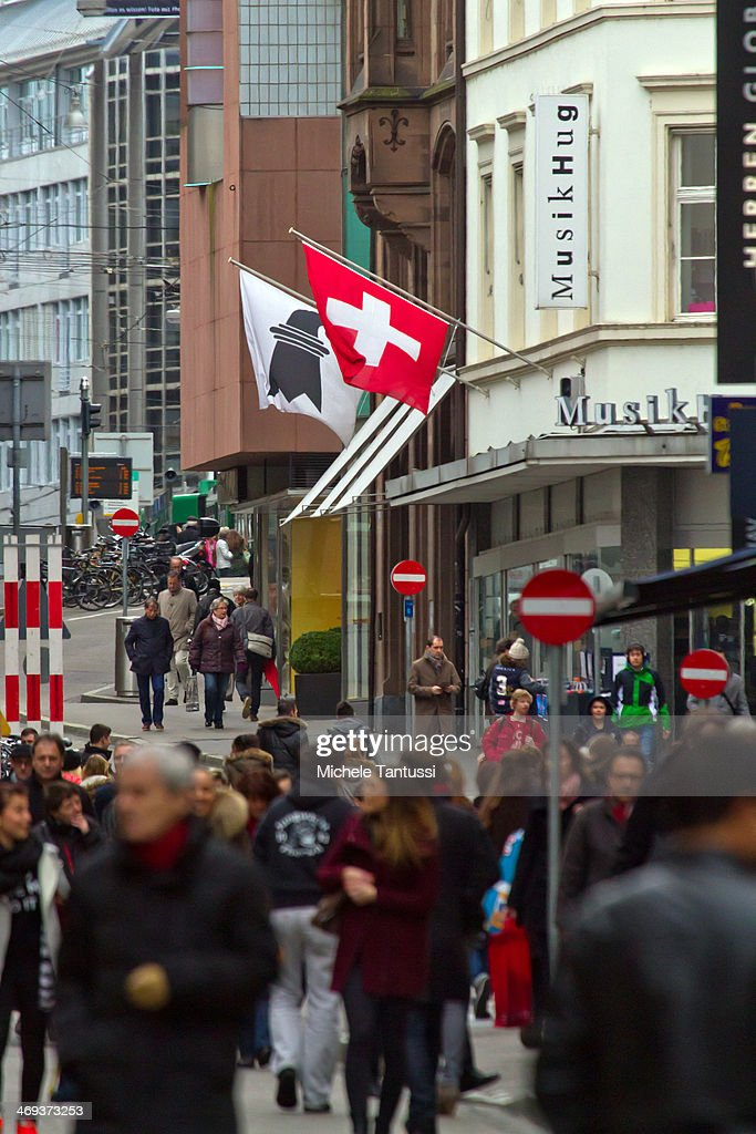 A Swiss National Flag waves as pedestrians walk in the Freie strasse on February 14, 2014 at Basel,Switzerland. Swiss citizens voted with a narrow majority in favour of measures to curb immigration from European Union countries in a move that will require Swiss officials to renegotiate several treaties with the EU. The referendum was launched by the right-wing Swiss People's Party (SVP). Approximately one quarter of people living in Switzerland are foreigners.