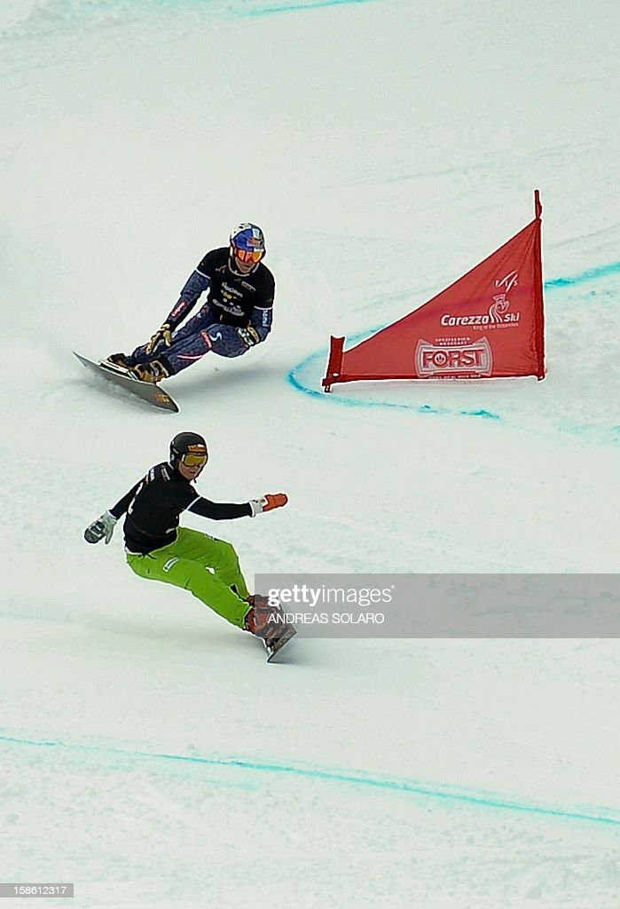 Swiss Nevin Galmarini (down) clears a gate with Austria's Benjamin Karl during the qualification run of the Snowboard FIS World Cup Parallel Giant Slalom race in Carezza in the Dolomites on December 21, 2012.