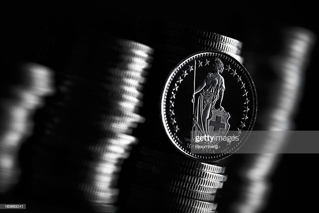 A Swiss one franc coin stands in front of other Swiss coins in this arranged photograph in Lavigny, Switzerland, on Wednesday, March 13, 2013. The Swiss central bank pledged to keep up its defense of the franc cap after almost doubling its currency holdings to shield the country from the fallout caused by the euro zone's crisis. Photographer: Valentin Flauraud/Bloomberg via Getty Images