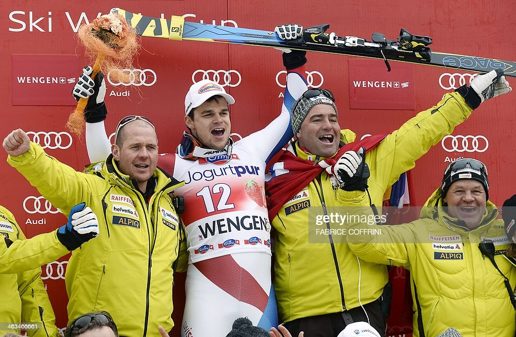 Swiss' Patrick Kueng celebrates his victory with team members on the podium of the FIS men's Alpine World Cup downhill in Wengen on January 18 2014...