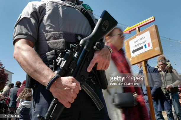 A Swiss police officer guards the entrance of a polling station for French citizen living in Switzerland during the first round of the French...