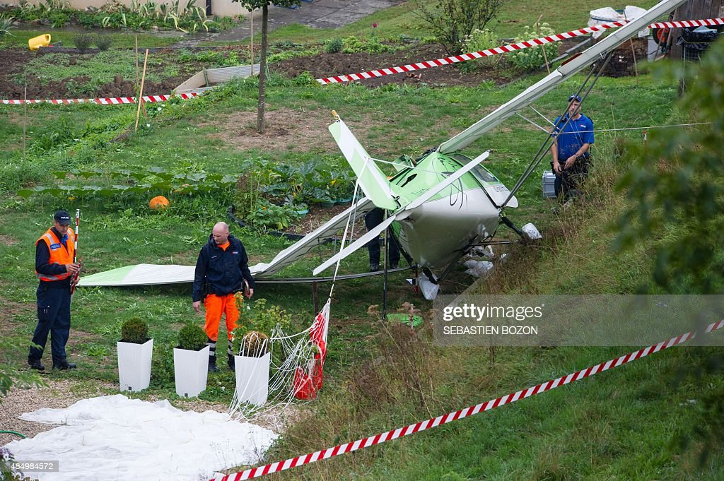 Swiss police officers inspect the wreckage of a plane involved in a collision with a second plane during an airshow on August 23 2015 in Dittingen...