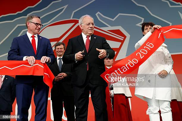 Swiss President Johann SchneiderAmmann cuts the ribbon next to Swiss Federal Railways CEO Andreas Meyer and Swiss Transport Minister Doris Leuthard...