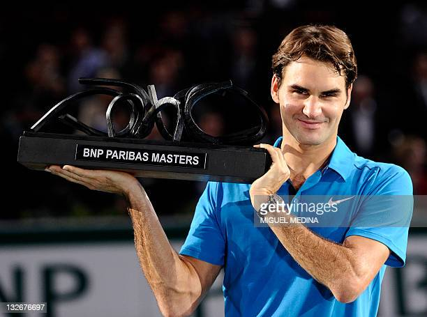 Swiss Roger Federer celebrates with his trophy after winning against French JoWilfried Tsonga their Paris Tennis Masters Series indoor tournament...