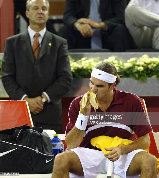 Swiss Roger Federer eats a banana under the eye of a security guard during his Masters Series match against Spaniard Alex Corretja in Madrid 15...