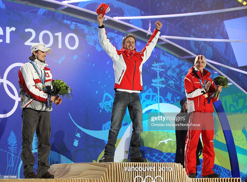 Swiss <a gi-track='captionPersonalityLinkClicked' href=/galleries/search?phrase=Simon+Ammann&family=editorial&specificpeople=210667 ng-click='$event.stopPropagation()'>Simon Ammann</a> (C) celebrates on the podium as Poland's <a gi-track='captionPersonalityLinkClicked' href=/galleries/search?phrase=Adam+Malysz&family=editorial&specificpeople=208124 ng-click='$event.stopPropagation()'>Adam Malysz</a> (L) and Austrian <a gi-track='captionPersonalityLinkClicked' href=/galleries/search?phrase=Gregor+Schlierenzauer&family=editorial&specificpeople=2963942 ng-click='$event.stopPropagation()'>Gregor Schlierenzauer</a> (R) look on during the medal ceremony for the Ski Jumping Normal Hill Individual event on day 2 of the Olympic Winter Games Vancouver 2010 ski jumping on February 13, 2010 in Whistler, Canada.