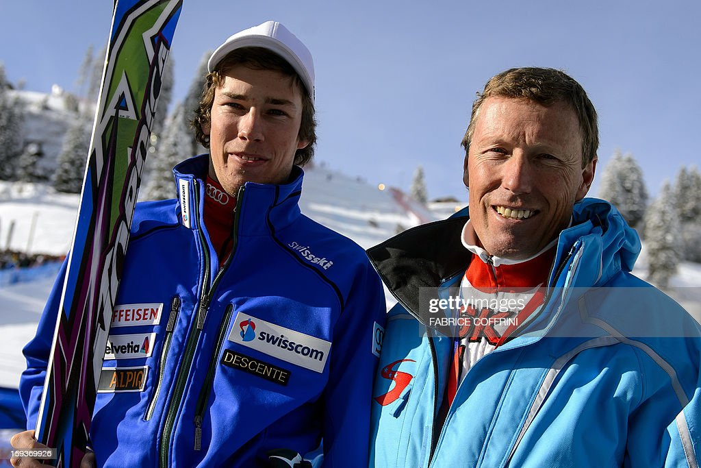Swiss ski legend Pirmin Zurbriggen (R) poses with his son Elia after the first run of the men's giant slalom race at the FIS Alpine Skiing World Cup on January 12, 2013 in Adelboden. Elia reced his first World cup race. AFP PHOTO / FABRICE COFFRINI