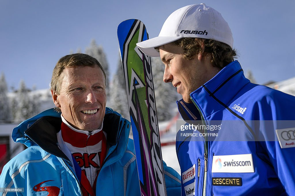Swiss ski legend Pirmin Zurbriggen (L) poses with his son Elia after the first run of the men's giant slalom race at the FIS Alpine Skiing World Cup on January 12, 2013 in Adelboden. Elia reced his first World cup race. AFP PHOTO / FABRICE COFFRINI
