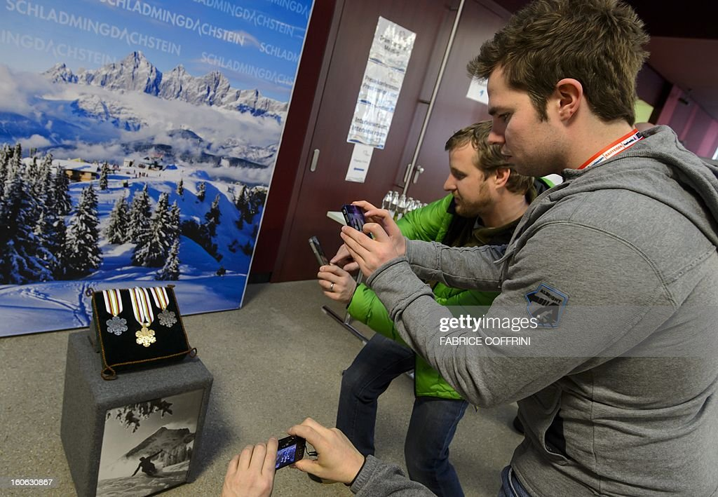 Swiss ski star Beat Feuz (2nd R), who was ruled out for the season after failing to recover fully from a knee operation, snaps with his mobile phone a picture of the upcoming 2013 Ski World Championships' medals on February 4, 2013 in Schladming. The February 4-17 World Ski Championships will feature male and female skiers racing in 11 events AFP PHOTO / FABRICE COFFRINI