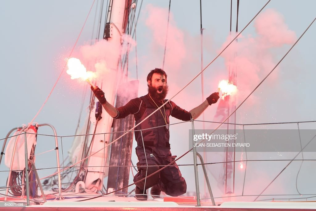 Swiss skipper Alan Roura, placing 12th in his first participation to the Vendee Globe around-the-world solo sailing race, celebrates aboard his Imoca 60 monohull 'La Fabrique' on February 20, 2017 as he arrives in Les Sables-d'Olonne, western France. /