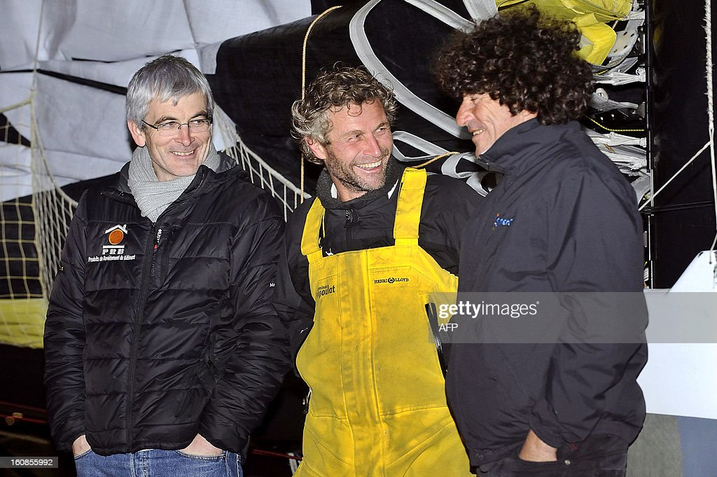 Swiss skipper Bernard Stamm (C) is welcomed by French skippers Vincent Riou (L) and Jean le Cam (R) upon his arrival late on February 6, 2013 in Les Sables d'Olonne, western France, after ending the 7th edition of the Vendee Globe solo round-the-world race. Stamm was disqualified on January 2, 2013, after receiving uncalled for assistance after his generator packed up but was later allowed to race on following a successful appeal to the race jury. Le Cam finished fifth of the event as Riou abandoned on November 24, 2012 after his hull was damaged by a metallic buoy. AFP PHOTO JEAN-SEBASTIEN EVRARD