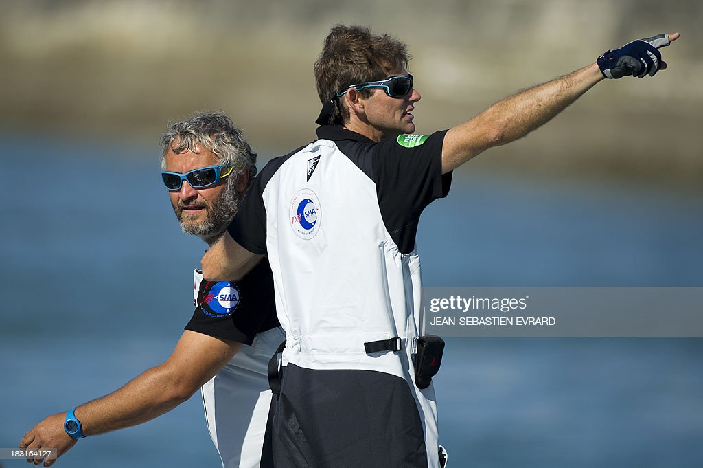 Swiss skipper Yvan Bourgnon (L) and French skipper Vincent Beauvarlet gesture as they take the start for a one-year trip around the world without assistance on their 6,40m multi hull 'Defi SMA'on October 5, 2013 in Les Sables d'Olonne, western France. AFP PHOTO / JEAN-SEBASTIEN EVRARD