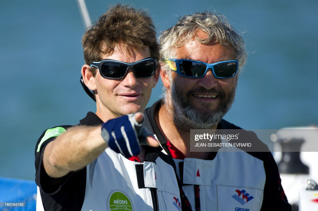 Swiss skipper Yvan Bourgnon (R) and French skipper Vincent Beauvarlet gesture as they take the start for a one-year trip around the world without assistance on their 6,40m multi hull 'Defi SMA'on October 5, 2013 in Les Sables d'Olonne, western France.