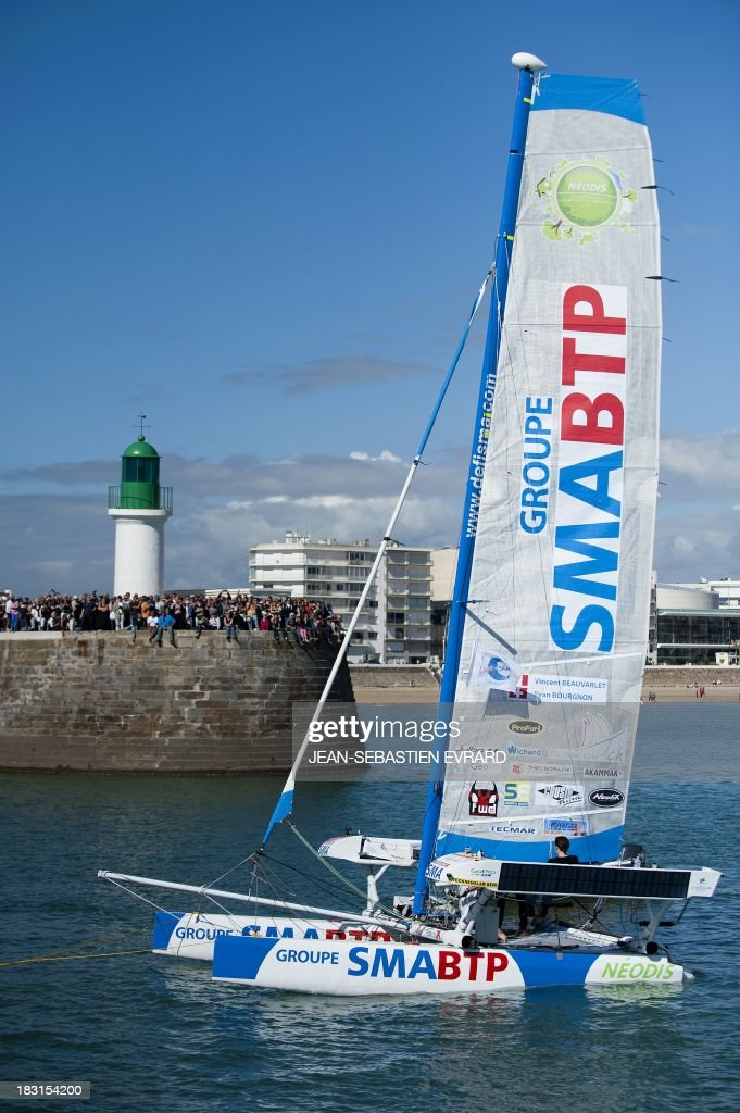 Swiss skipper Yvan Bourgnon and French skipper Vincent Beauvarlet take the start of a one-year trip around the world without assistance on their 6,40m multi hull 'Defi SMA'on October 5, 2013 in Les Sables d'Olonne, western France.