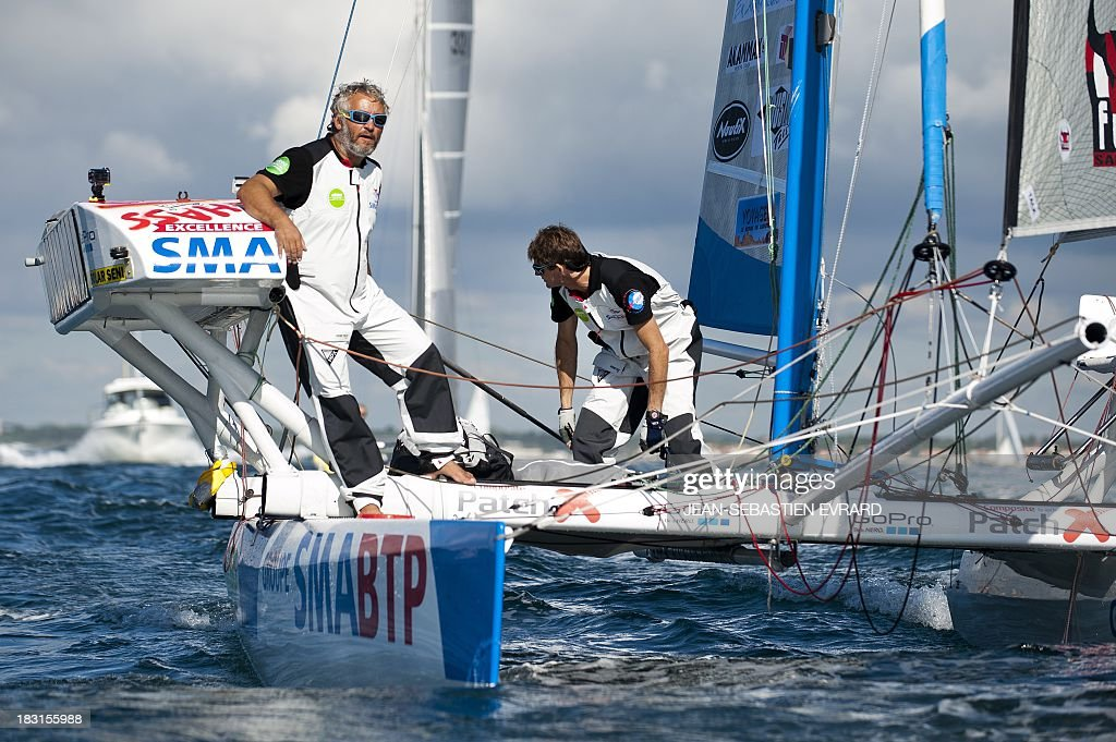 Swiss skipper Yvan Bourgnon (L) and French skipper Vincent Beauvarlet (R) take the start of a one-year trip around the world without assistance on their 6,40m multi hull 'Defi SMA'on October 5, 2013 in Les Sables d'Olonne, western France.