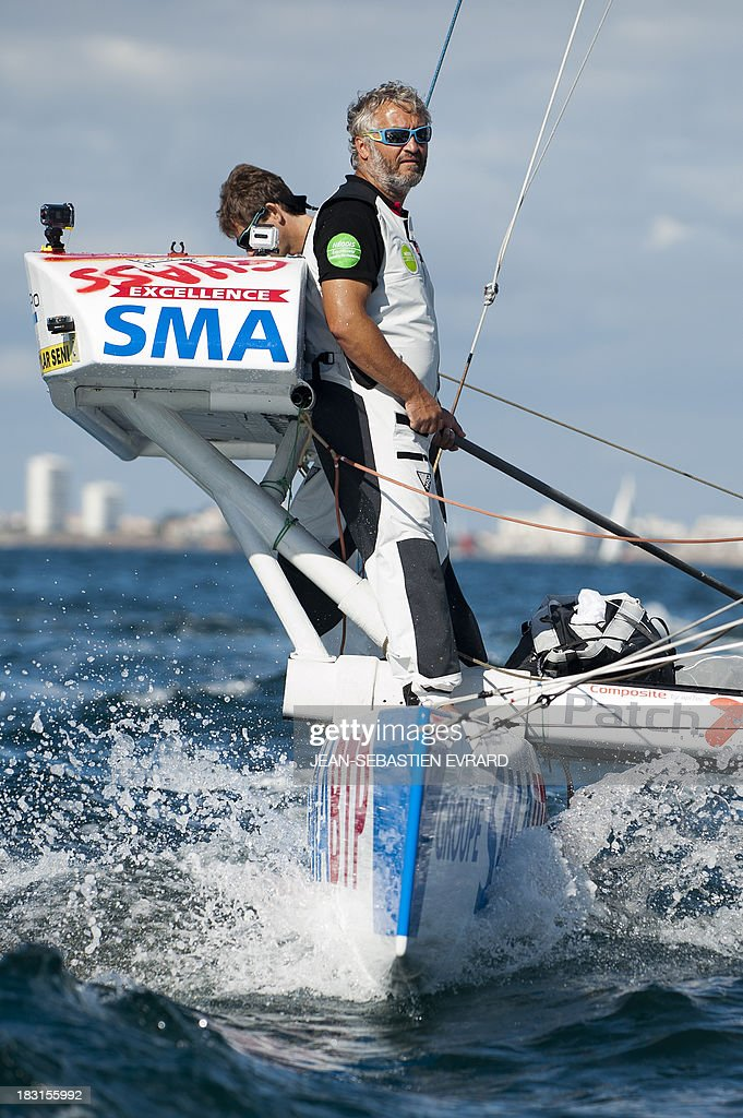 Swiss skipper Yvan Bourgnon (R) and French skipper Vincent Beauvarlet (L) take the start of a one-year trip around the world without assistance on their 6,40m multi hull 'Defi SMA'on October 5, 2013 in Les Sables d'Olonne, western France.