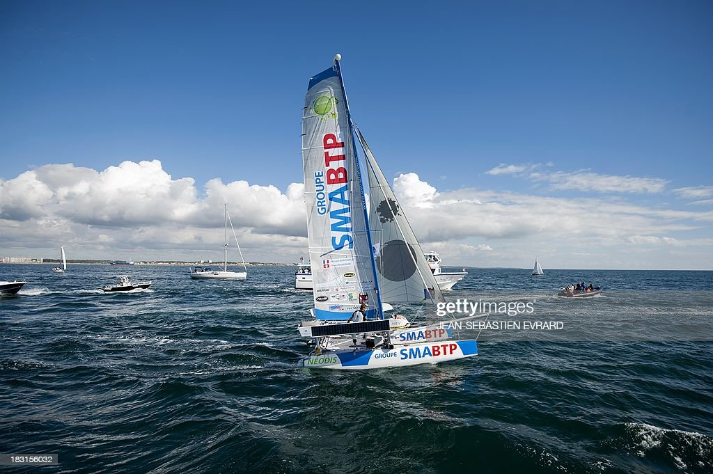Swiss skipper Yvan Bourgnon and French skipper Vincent Beauvarlet take the start of a one-year trip around the world without assistance on their 6,40m multi hull 'Defi SMA'on October 5, 2013 in Les Sables d'Olonne, western France. AFP PHOTO / JEAN-SEBASTIEN EVRARD