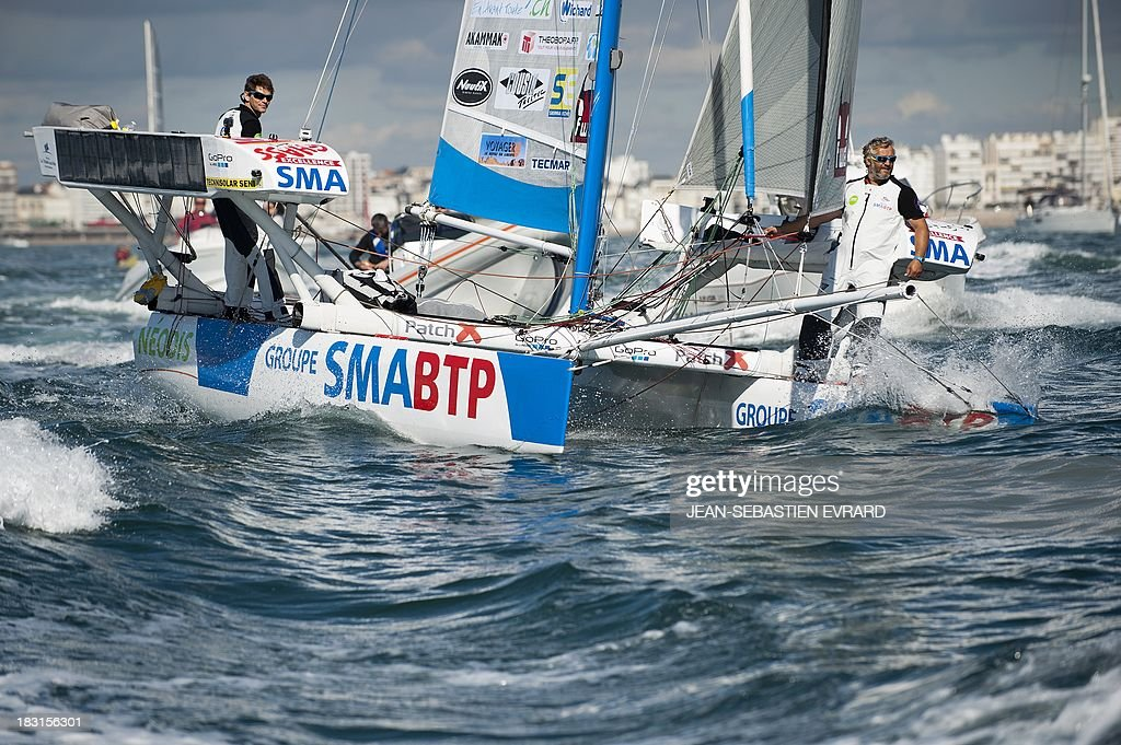 Swiss skipper Yvan Bourgnon (R) and French Vincent Beauvarlet take the start for one-year trip around the world without assistance on their 6,40m multi hull 'Défi SMA'on october 5, 2013 in Les Sables d'Olonne, western France. AFP PHOTO / JEAN-SEBASTIEN EVRARD