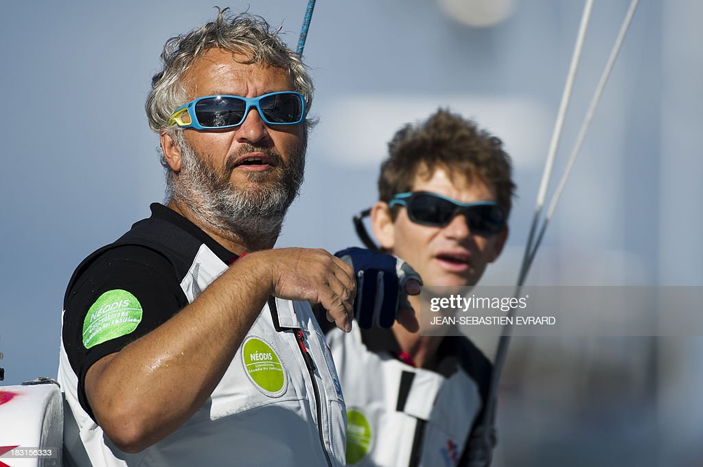 Swiss skipper Yvan Bourgnon (L) and French Vincent Beauvarlet take the start of a one-year trip around the world without assistance on their 6,40m multi hull 'Défi SMA'on october 5, 2013 in Les Sables d'Olonne, western France.