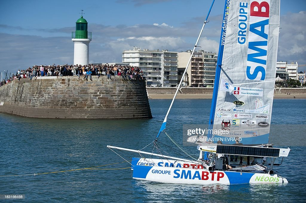 Swiss skipper Yvan Bourgnon and French Vincent Beauvarlet take the start of a one-year trip around the world without assistance on their 6,40m multi hull 'Défi SMA'on october 5, 2013 in Les Sables d'Olonne, western France.
