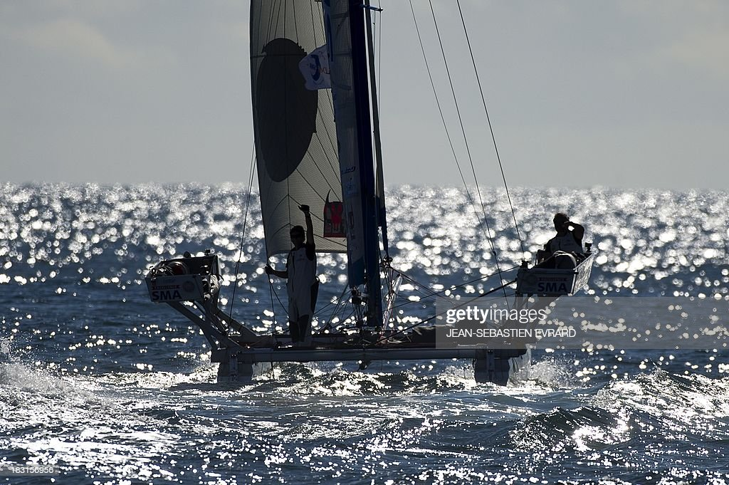Swiss skipper Yvan Bourgnon and French Vincent Beauvarlet wave as they depart on a round the world trip on a catamaran on October 5, 2013 from Les Sables d'Olonne. The pair plan to take 11 months to cover the trip on a 6.3metre catamaran. EVRARD